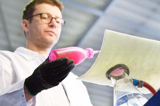 De mens met witte laag in laboratorium houdt fles roze vloeistof over cipp liner proefstuk
